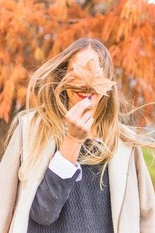 Blonde frau, die auf wind mit herbstblatt steht