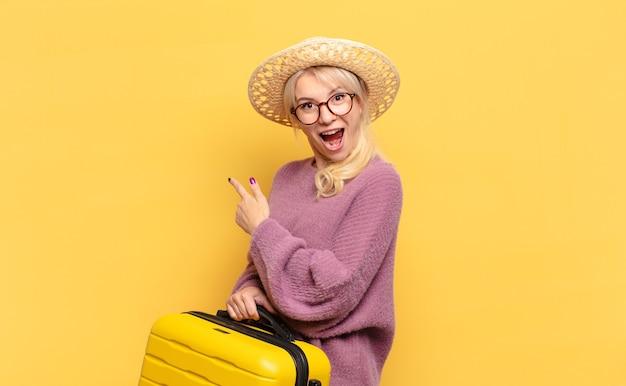 Blonde frau, die aufgeregt und überrascht aussieht und zur seite und nach oben zeigt, um raum zu kopieren