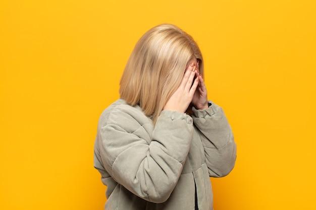 Blonde frau, die augen mit händen mit einem traurigen, frustrierten blick der verzweiflung, des weinens, der seitenansicht bedeckt