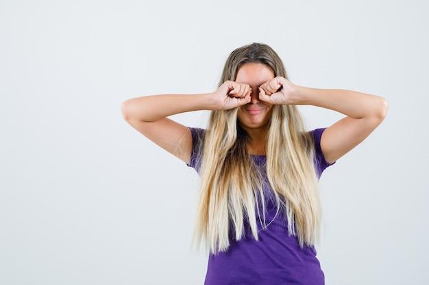 Blonde frau, die augen reibt, während sie im violetten t-shirt weint und beleidigt, vorderansicht schaut.