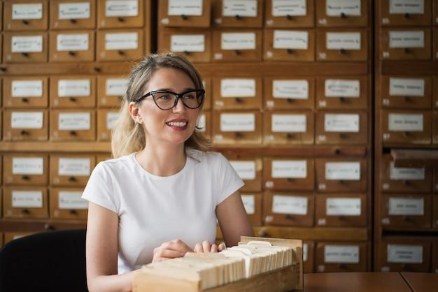 Blonde frau, die buchdateien in der bibliothek sucht