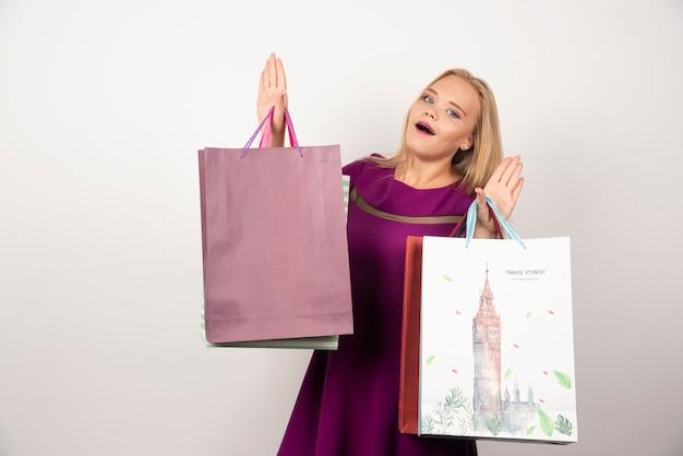 Blonde frau, die bündel bunte einkaufstaschen hält.