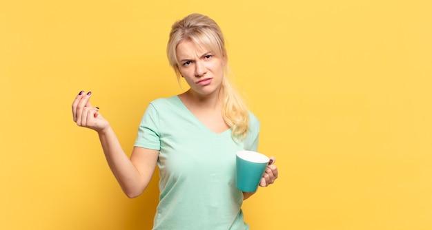 Blonde frau, die capice oder geldgeste macht und ihnen sagt, dass sie ihre schulden bezahlen sollen!