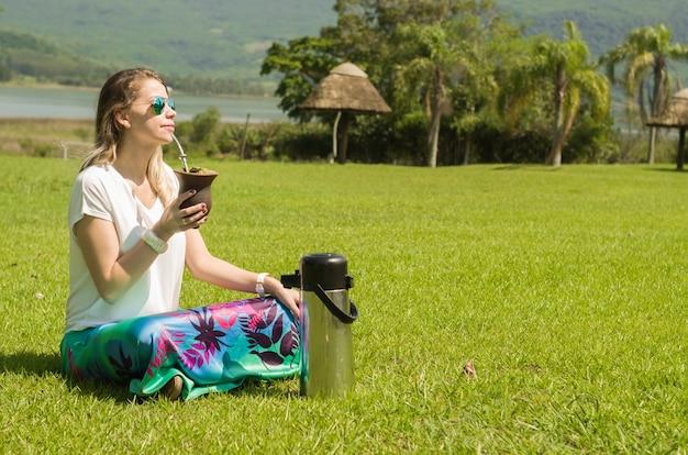 Blonde frau, die das traditionelle chimarrao aus dem bundesstaat rio grande do sul in brasilien trinkt.