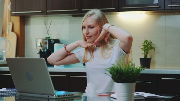 Blonde frau, die die musik hört und ihre arme vor dem computer hebt