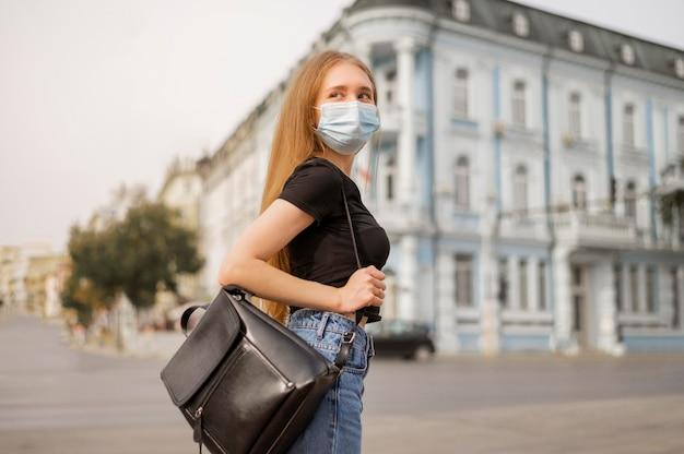 Blonde frau, die draußen eine medizinische maske trägt