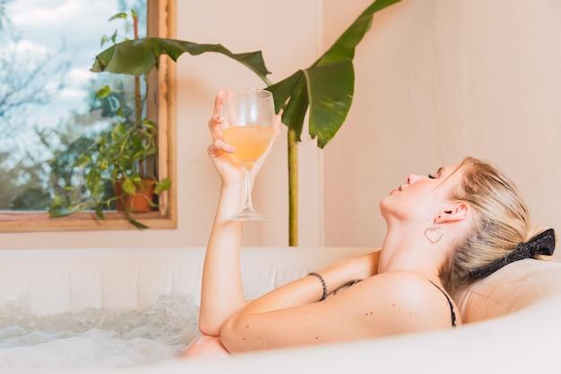 Blonde frau, die ein bad im jacuzzy genießt. junge frau, die mit einem glas wein im whirlpool liegt. menschen, schönheit, spa, gesunder lebensstil und entspannungskonzept.