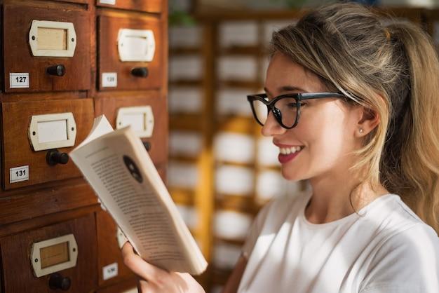 Blonde frau, die ein buch in der bibliothek liest