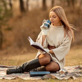 Blonde frau, die ein buch liest