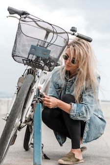 Blonde frau, die ein fahrradschloss setzt
