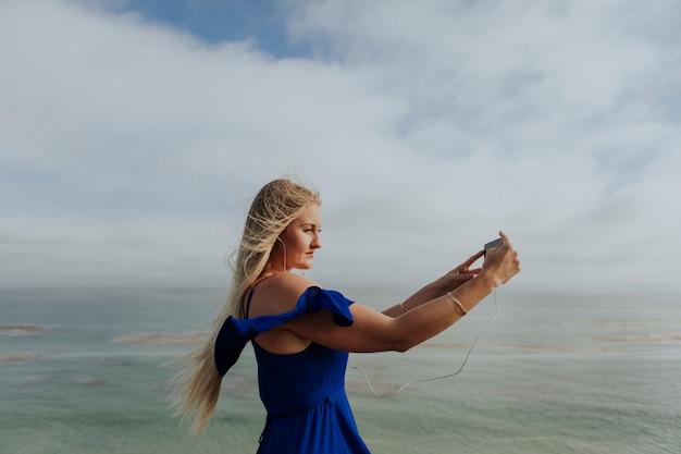 Blonde frau, die ein foto mit ihrem telefon macht