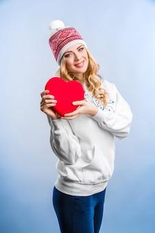 Blonde frau, die ein rotes herz hält. valentinstag