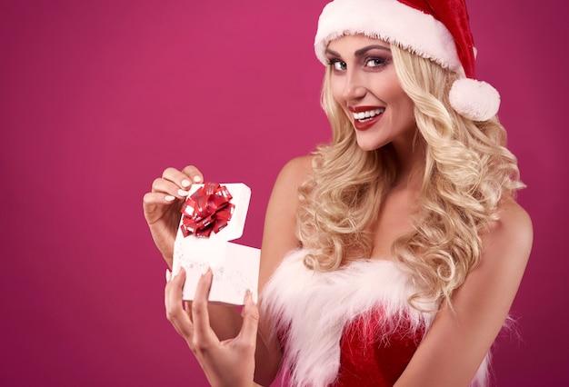 Blonde frau, die ein weihnachtsgeschenk öffnet
