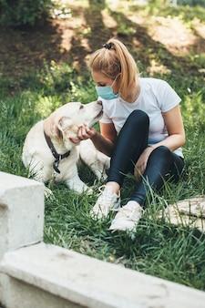 Blonde frau, die eine antivirenmaske trägt, die mit ihrem labrador auf dem gras liegt