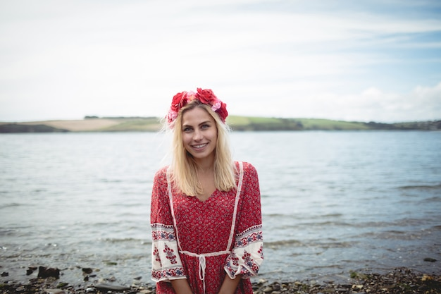 Blonde frau, die eine blumentiara trägt, die nahe einem fluss sitzt
