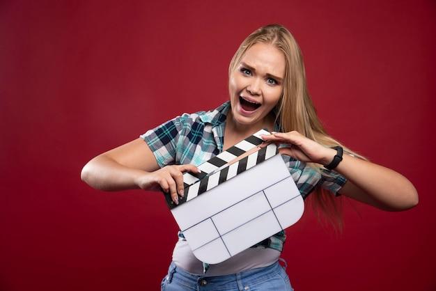 Blonde frau, die eine filmproduktionsklappe hält und positiv und lustig aussieht.