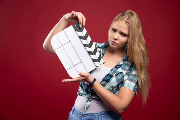Blonde frau, die eine filmproduktionsklappe hält und sieht verwirrt und müde aus.