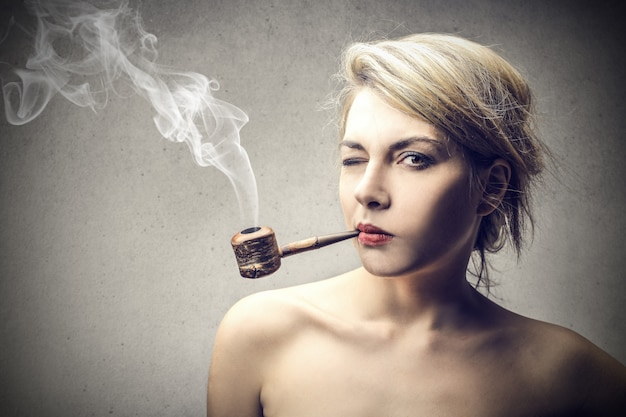Blonde frau, die eine pfeife raucht