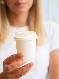 Blonde frau, die eine plastikkaffeetasse zeigt