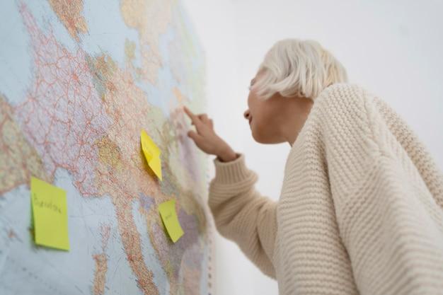 Blonde frau, die eine reise mit einer karte plant