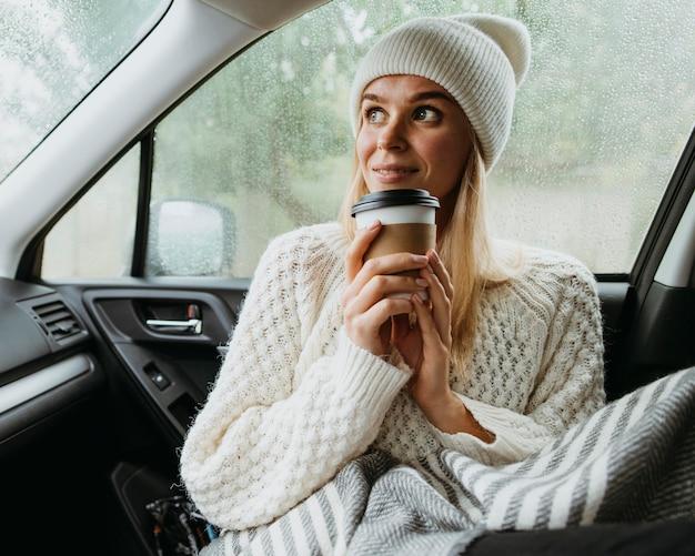 Blonde frau, die eine tasse kaffee in einem auto hält