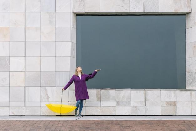Blonde frau, die einen lila mantel und einen gelben regenschirm auf einem steinarchitekturhintergrund mit einem großen fenster trägt