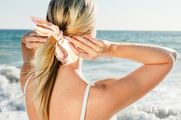 Blonde frau, die einen pferdeschwanz am strand zurück bindet