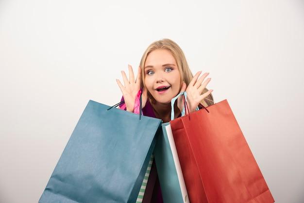 Blonde frau, die einkaufstaschen mit glücklichem ausdruck hält.