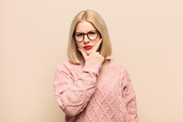 Blonde frau, die ernst, nachdenklich und misstrauisch aussieht, mit einem arm verschränkt und hand am kinn, gewichtungsoptionen