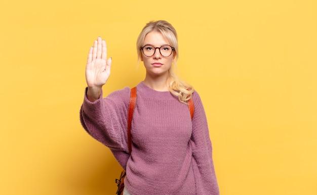 Blonde frau, die ernst, streng, unzufrieden und wütend aussieht und offene handfläche zeigt, die stoppgeste macht