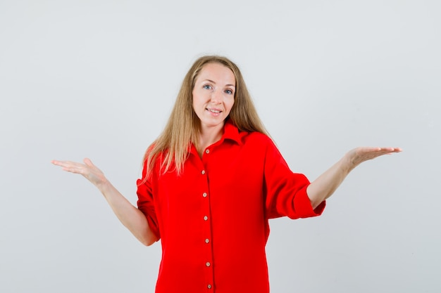 Blonde frau, die etwas im roten hemd präsentiert oder vergleicht und fröhlich aussieht.