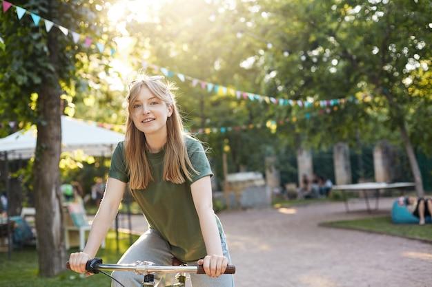 Blonde frau, die fahrrad fährt. porträt der jungen nordischen frau, die ein fahrrad in einem lächelnden lebensstilkonzept des stadtparks reitet.