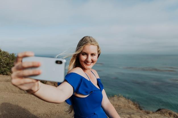 Blonde frau, die fotos mit ihrem telefon macht