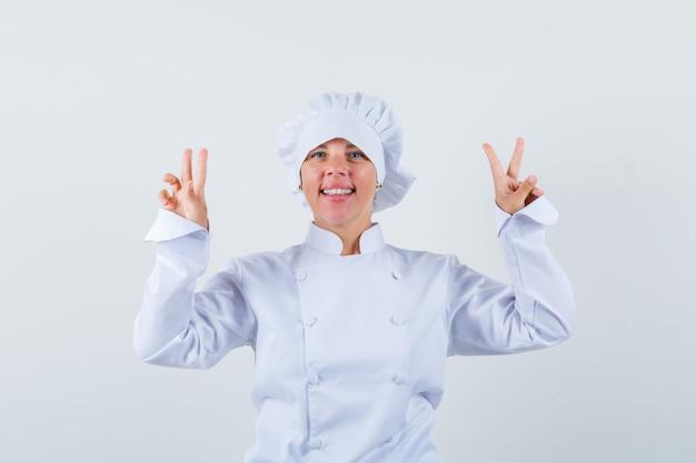 Blonde frau, die friedenszeichen mit beiden händen in der weißen kochuniform zeigt und hübsch aussieht