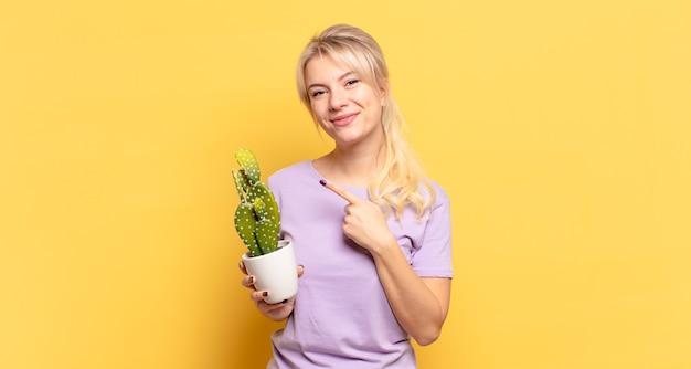 Blonde frau, die fröhlich lächelt, sich glücklich fühlt und zur seite und nach oben zeigt und das objekt im kopierraum zeigt