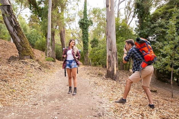 Blonde frau, die für foto auf straße im wald aufwirft. kaukasischer mann, der kamera hält und auf natur schießt. zwei glückliche leute, die mit rucksäcken wandern. tourismus-, abenteuer- und sommerferienkonzept