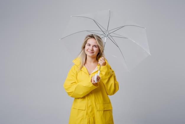 Blonde frau, die gelben regenmantel hält, der transparenten regenschirm hält, der wetter überprüft, wenn es regnet