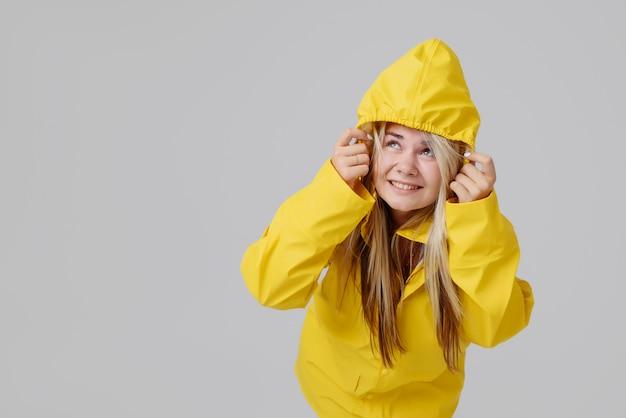 Blonde frau, die gelben regenmantel trägt
