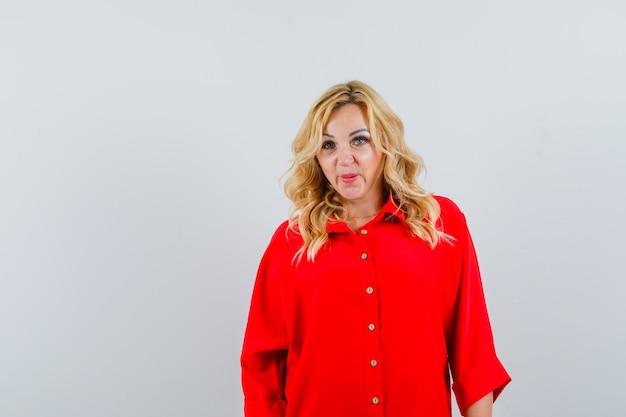 Blonde frau, die gerade steht und an der kamera in der roten bluse aufwirft und ernst schaut.