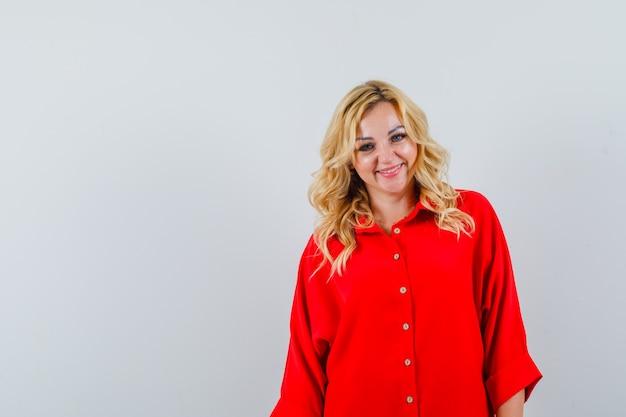 Blonde frau, die gerade steht und an der kamera in der roten bluse aufwirft und glücklich schaut