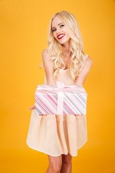 Blonde frau, die geschenk hält.