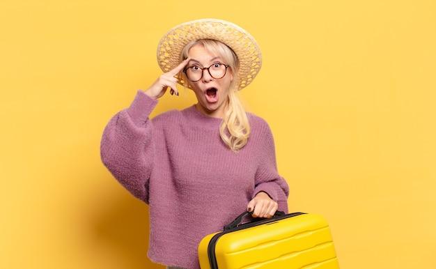 Blonde frau, die glücklich, erstaunt und überrascht aussieht, lächelt und erstaunliche und unglaublich gute nachrichten realisiert