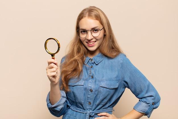 Blonde frau, die glücklich mit einer hand auf hüfte und selbstbewusster, positiver, stolzer und freundlicher haltung lächelt