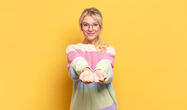 Blonde frau, die glücklich mit freundlichem, selbstbewusstem, positivem blick lächelt und ein objekt oder konzept anbietet und zeigt