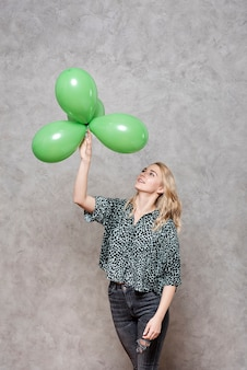 Blonde frau, die grüne ballone betrachtet