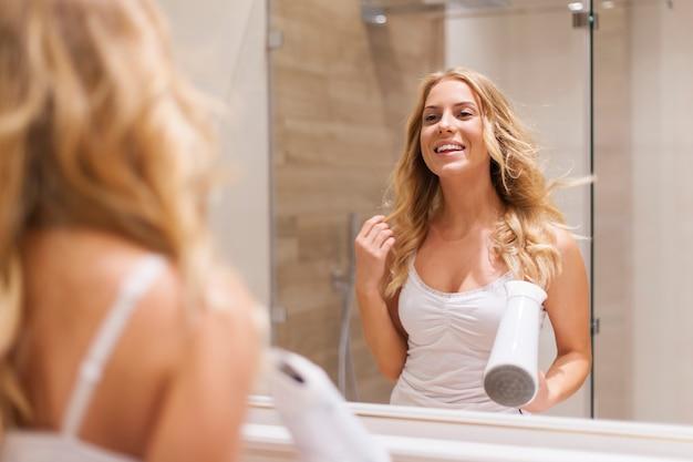 Blonde frau, die haare vor dem spiegel trocknet