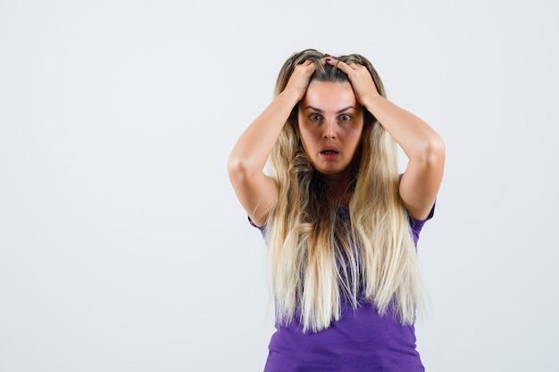 Blonde frau, die hände im haar im violetten t-shirt hält und wehmütig, vorderansicht schaut.