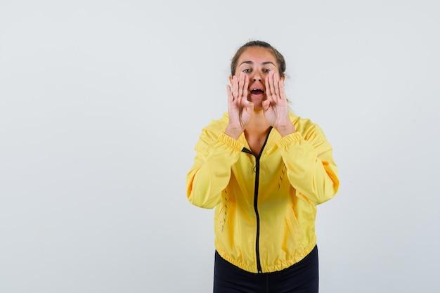 Blonde frau, die hände nahe mund hält, als jemand in gelber bomberjacke und in schwarzen hosen anrufend und glücklich aussehend