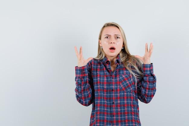 Blonde frau, die hände streckt und im karierten hemd nervös wird und schockiert schaut, vorderansicht.