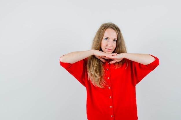 Blonde frau, die hände unter kinn im roten hemd hält und anmutig schaut,